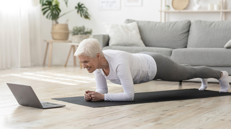 Sporty senior woman doing yoga plank while watching tutorial on laptop