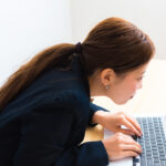 Image of woman using laptop while sitting at her desk