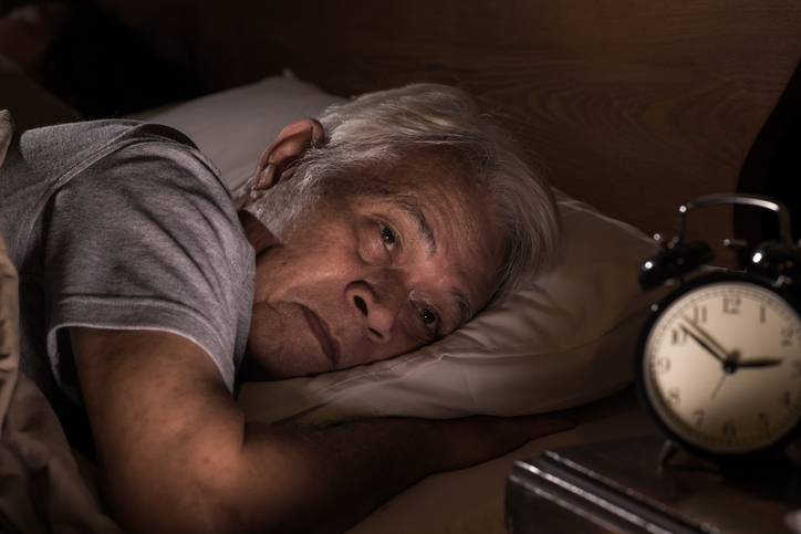 A depressed senior man lying in bed cannot sleep from insomnia