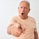 Senior grey-haired man wearing striped t-shirt standing over isolated white background pointing displeased and frustrated to the camera, angry and furious with you