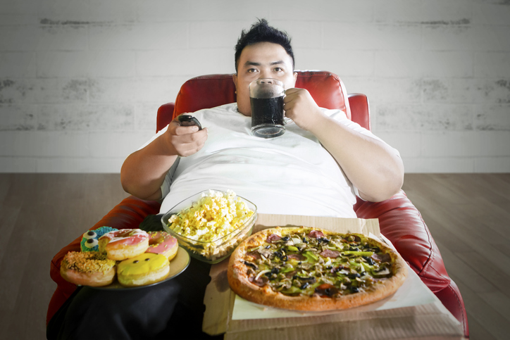 Young fat man enjoying junk foods on the sofa