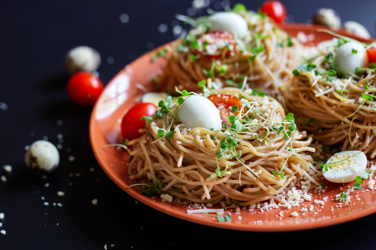 Buckwheat noodles with quail eggs, tomatoes and microgreen. Selective focus.