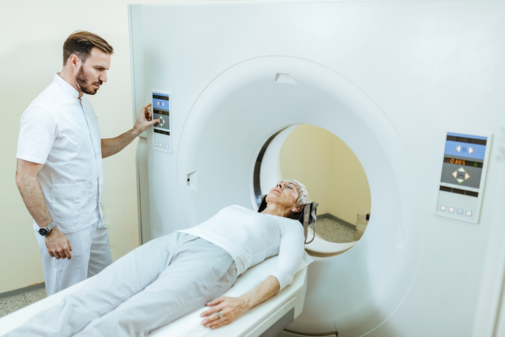 Mature woman undergoing MRI scan examination at medical clinic.