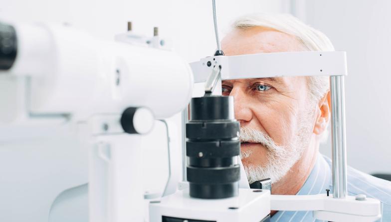 Senior man getting eye exam at clinic, close-up