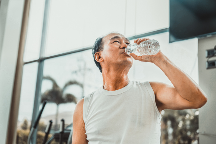 Senior man drink mineral water in fitness center.