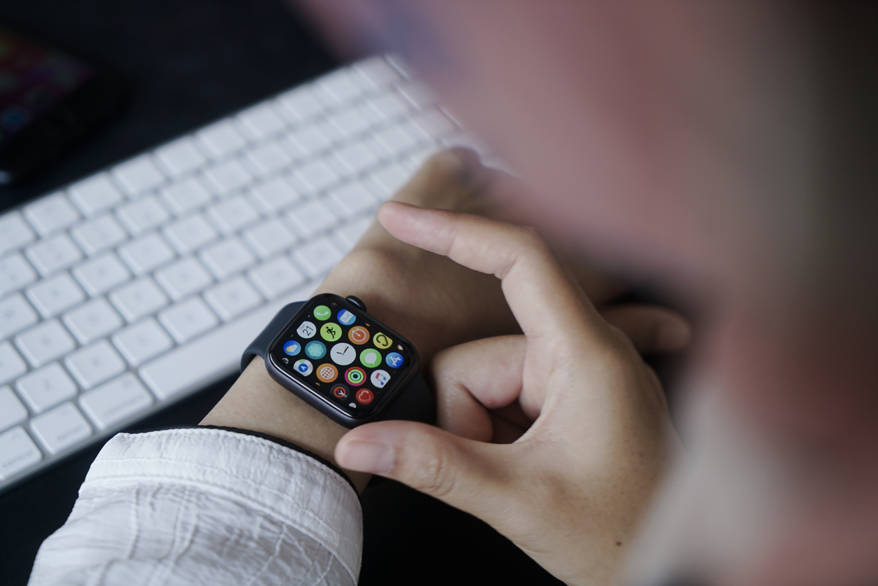 Close up Woman using Smart watch with keyboard background