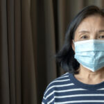 Portrait of Asian elder senior old female wearing face medical mask. pandemic coronavirus disease quarantine in home. Covid-19 outbreak prevention concept.