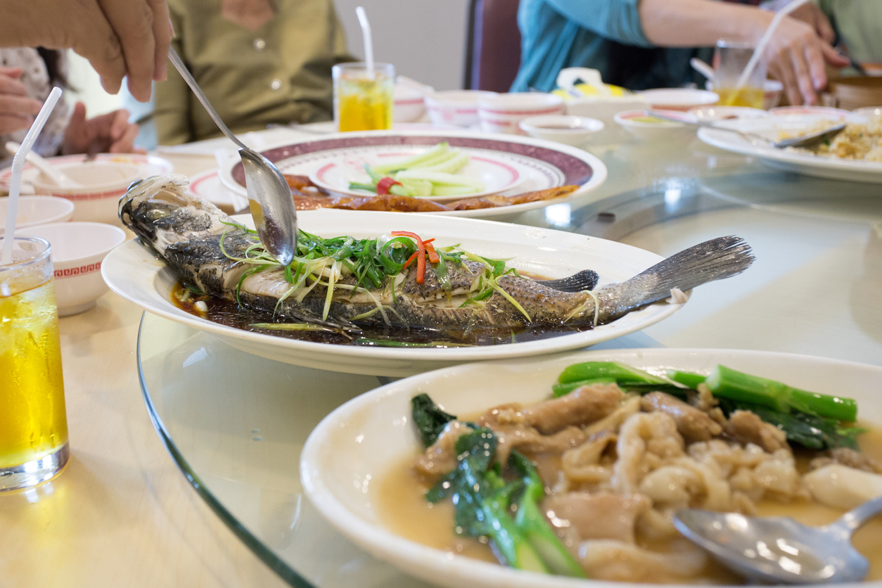 steam snapper fish with vegetable top on white dish, Chinese food