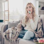 Portrait of nice lovely attractive funny hungry wavy-haired lady holding in hands cup eating large plate of tempting seductive sweets enjoying life in light interior room