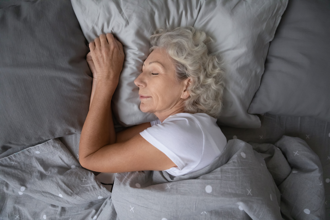 Happy mature woman sleeping on soft pillow under blanket.