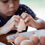 Asian little girl helping mother to peel egg