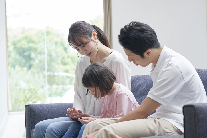 Asian family using the smartphone on the sofa