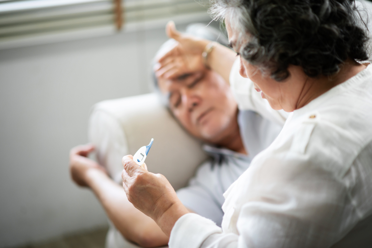 Asian Senior man lying on sofa while his wife holding and looking to thermometer.