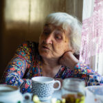 Portrait of an elderly russian woman sitting in the kitchen.