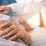 Hospitalized elderly patient, senior old aging woman laying on bed with cardiologist doctor or physician examining cardiological heart health, checking pulse in hospital clinic exam room