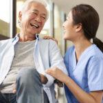 friendly asian caretaker talking to senior patient in nursing home