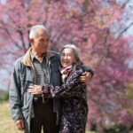 Happy old couple smiling in a park.mature couple with cherry blossom sakura tree.seniors lover family and healthcare concept.