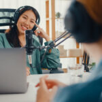 Asia girl radio host record podcast use microphone wear headphone interview celebrity guest content conversation talk and listen in her room.